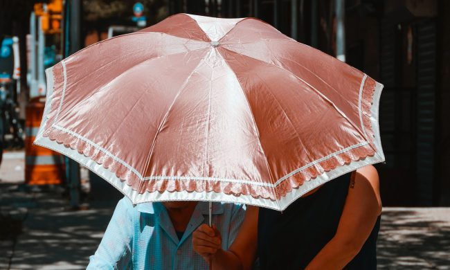 Woman holding umbrella for another woman